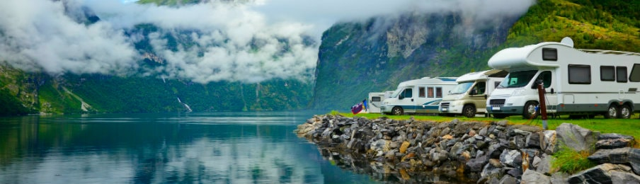 Campervan rentals parked on the side of the lake, NZ