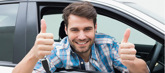 man inside the car rental showing thumbs up while holding a key in gisborne airport