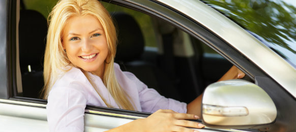 Beautiful woman smiling while inside her car