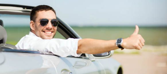 happy man driving car and showing thumbs up in east tamaki