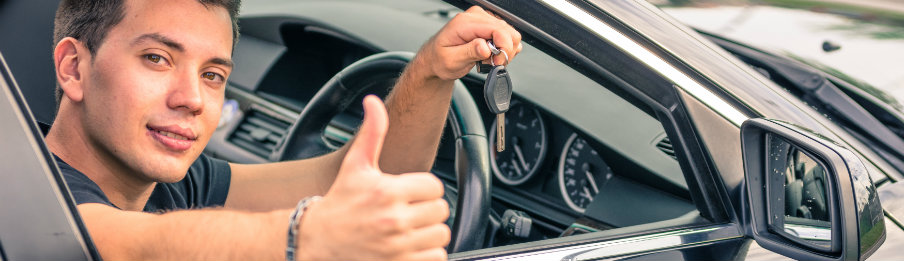 A man showing a car hire key and thumbs up while driving in canada