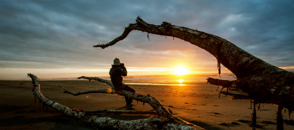 photographer taking photo of the sunset in black beach, hokitika