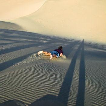sandboarder goes down the dune