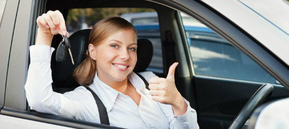 woman holding a key and showing thumbs up while inside the car rental in cambridge